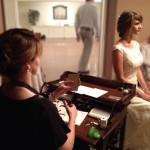 Silhouette artist, Patti Rishforth, hand cutting the bride's silhouette while guests watch.