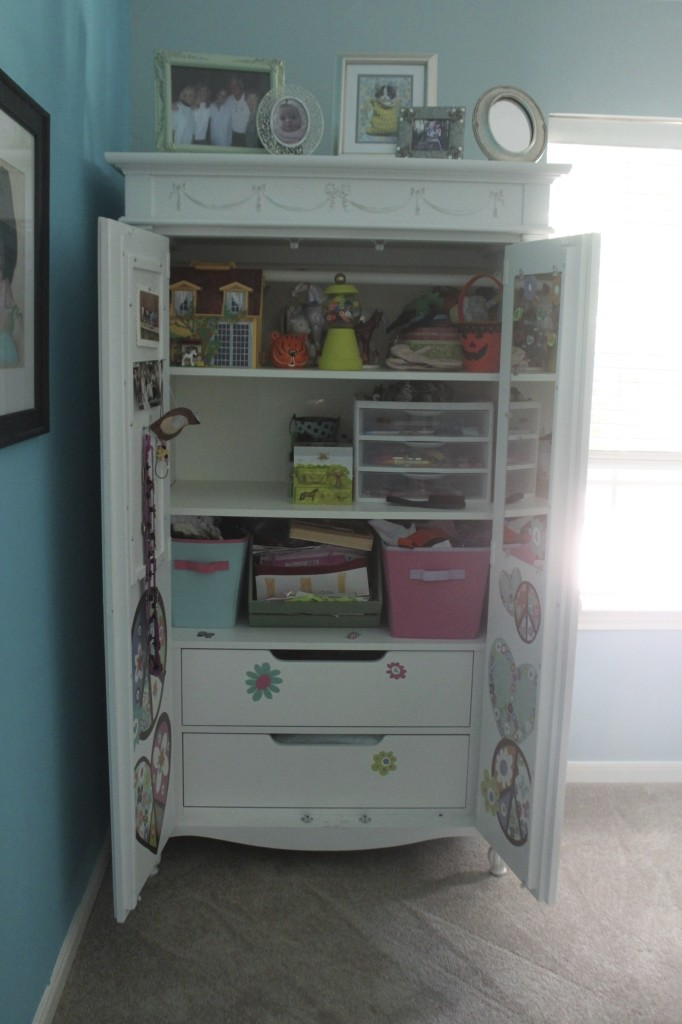 Girls have so many itty bitty collections of things. Most of that goes inside the armoire - along with some peace decals to make it more personalized.