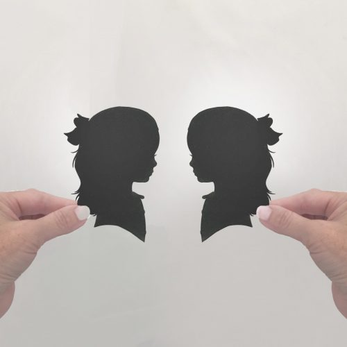 hands holding paper silhouettes